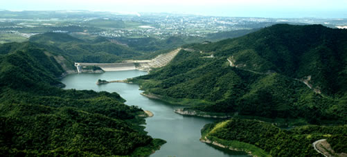 Image of a green river valley with a dam on one end.