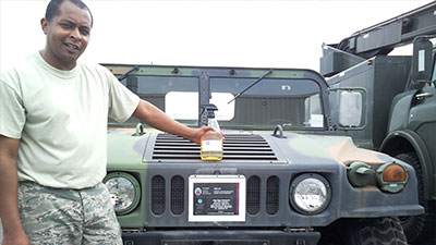 Image of a man with a cleaning product in front of a Jeep.